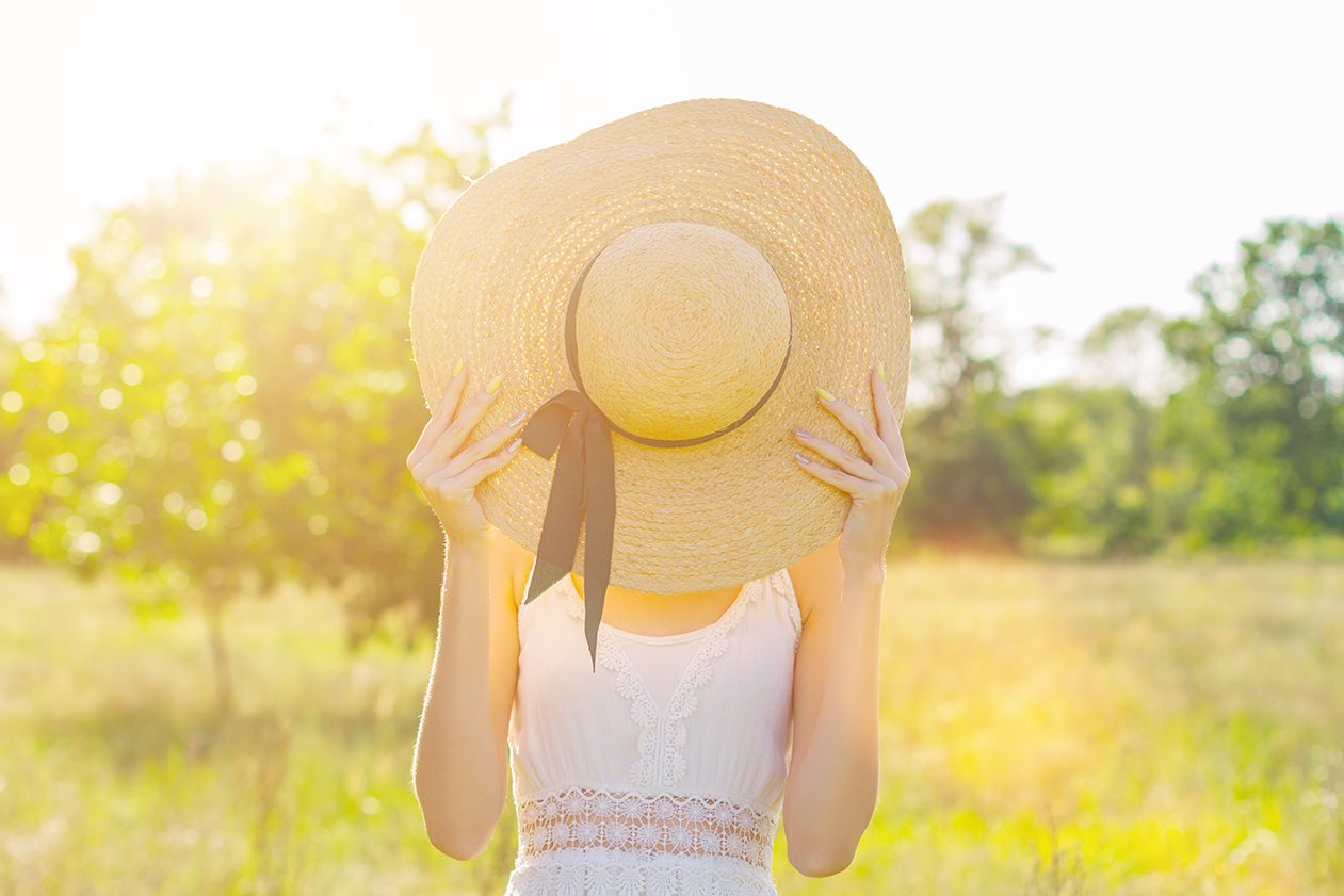 Woman with hat hiding her face in sunny field